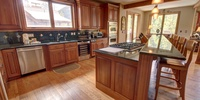 The kitchen has granite countertops and stainless steel appliances with a full sized fridge