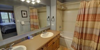 A big bathroom with dual sinks and a bath/shower
