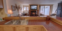 Kitchen with lots of counter space, also has view of the cozy fireplace and relaxing flat screen TV