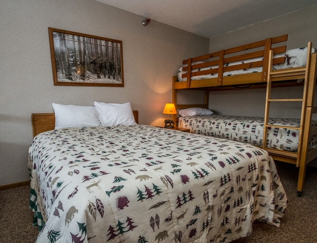 The loft bedroom features a queen bed and twin over twin bunk beds.