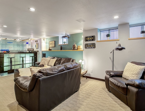 Basement Living Area with Seating, Pullout Mattress, & Bar.