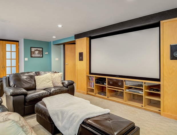 Basement Living Area with Seating, Pullout Mattress, & Projection TV for Streaming