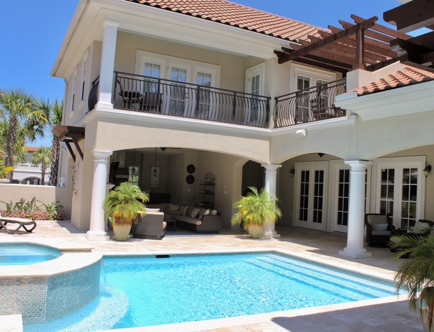 Pool with views of outdoor living area, outdoor kitchen, and balconies.