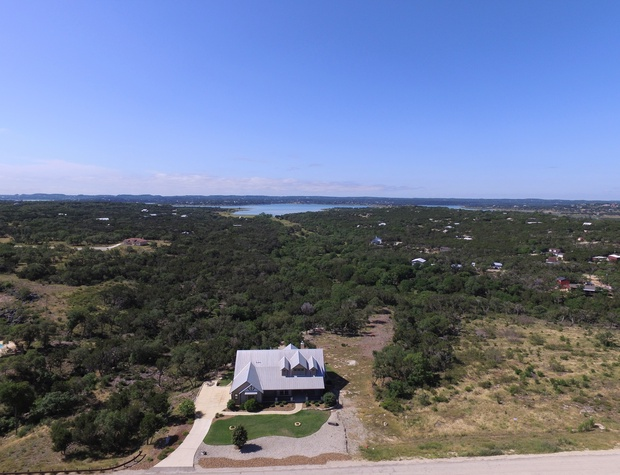 Aerial view of home with Canyon Lake in background.