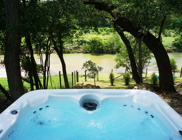 Enjoy river views from the private hot tub!