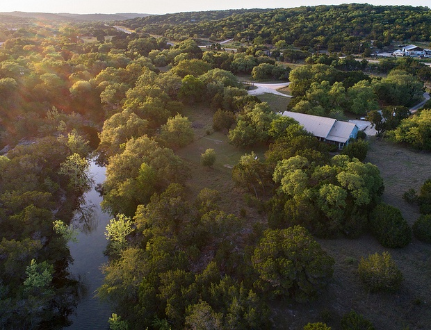 Aerial view of property looking at creek and home