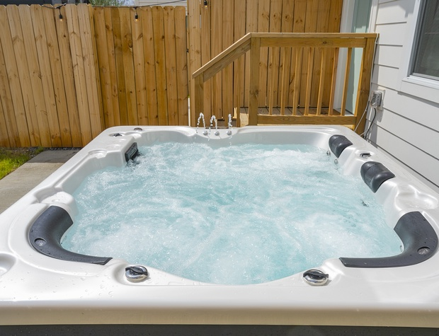 The hot tub is just outside the back door, next to the first level bedroom.