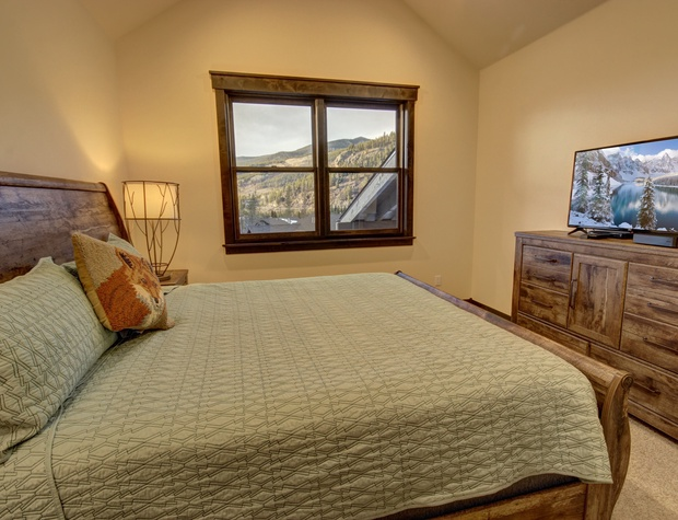 Bedroom with mountain view, dresser and flatscreen TV
