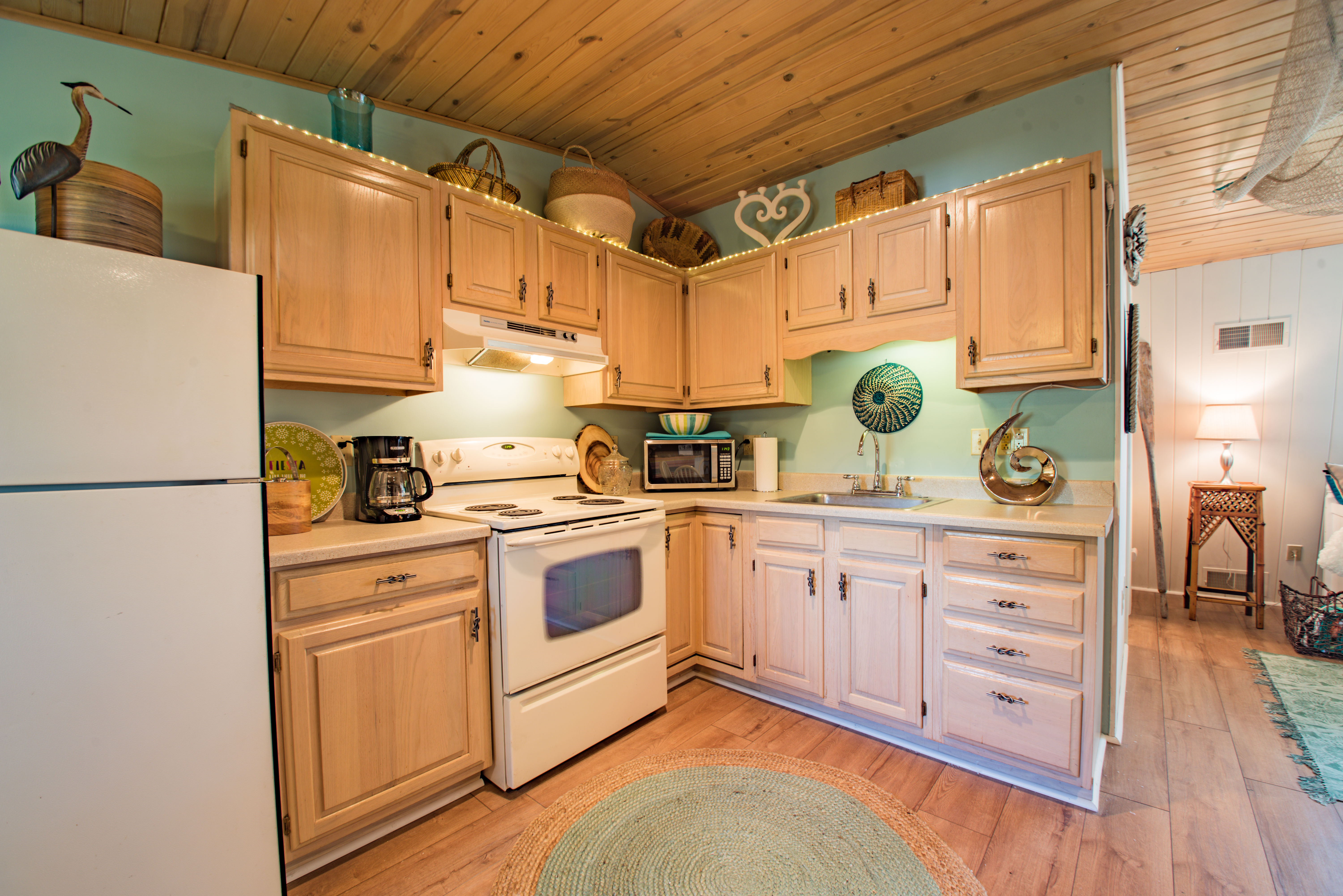 Fully equipped kitchen with coffee maker, oven, toaster, and refrigerator/freezer.
