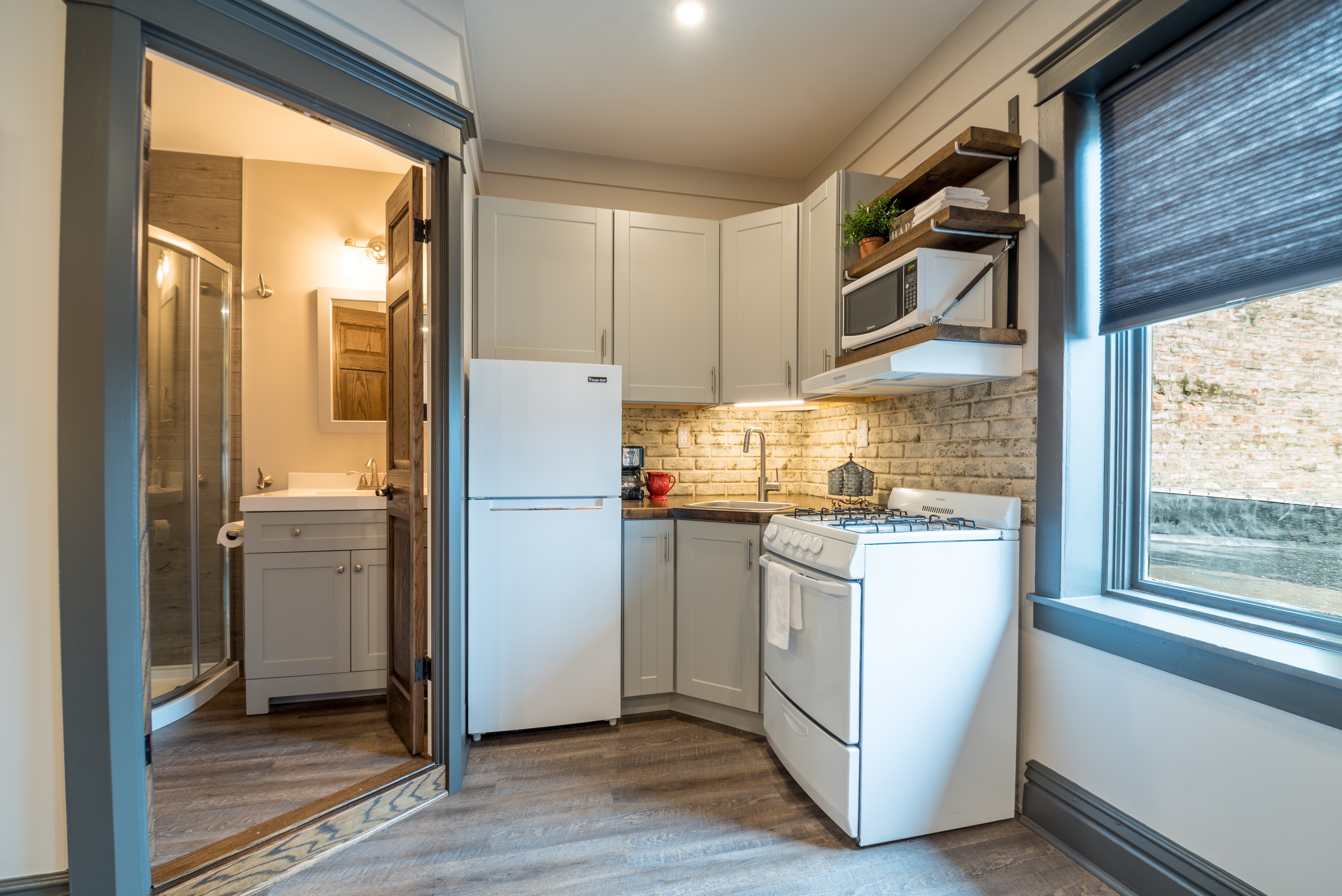 Boutique kitchen with apartment sized refrigerator/freezer, oven, microwave, coffee maker and sink